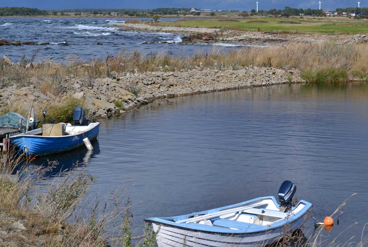 Alles auf einem Foto: Boote, Küste, See, Golfplatz und Windturbinen