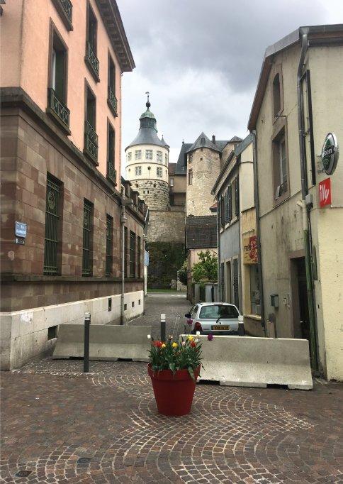 Gasse mit LKW-Sperre und im Hintergrund die Burg