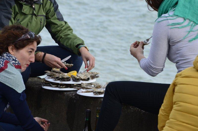 Austernessen auf der Hafenmauer