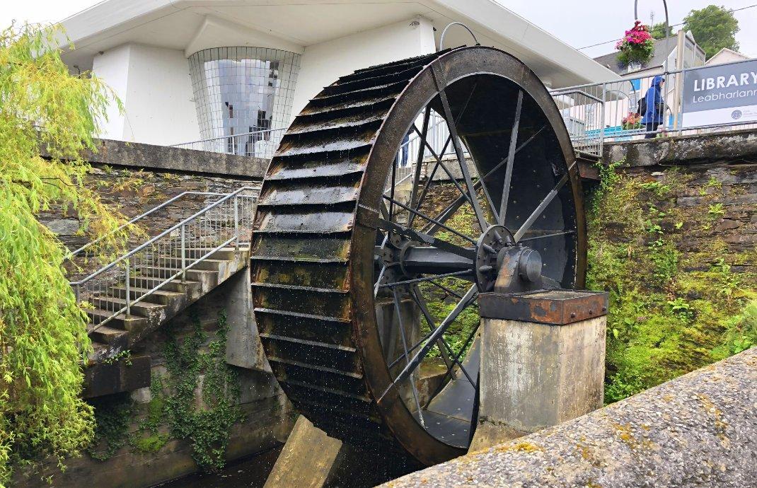 Altes Mühlenrad vor modernem Gebäude in Bantry