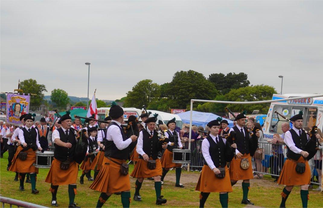 Viele Gruppen in schottischen Röcken mit Dudelsäcken