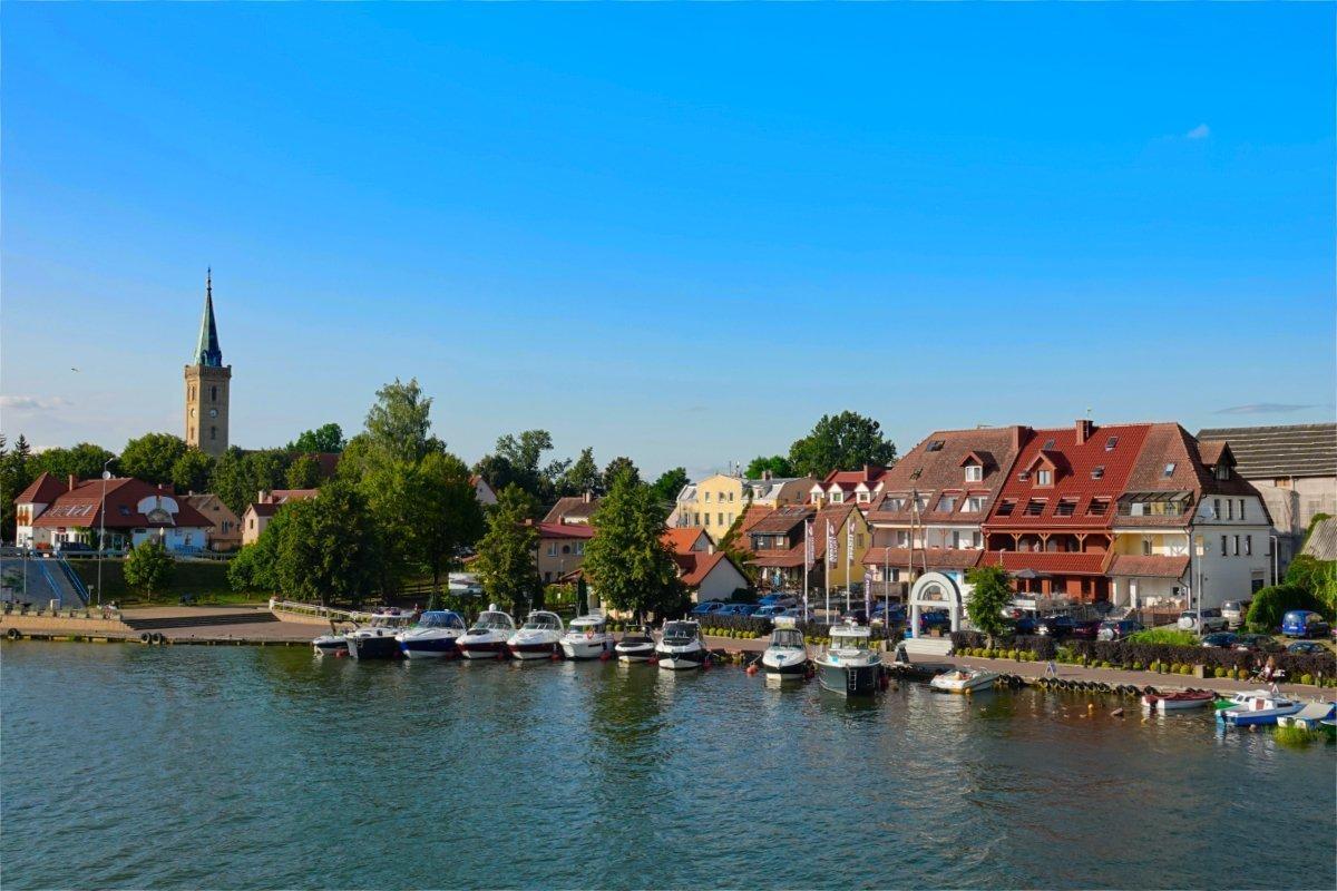 Vertaute Boote am Seeufer und evangelische Kirche