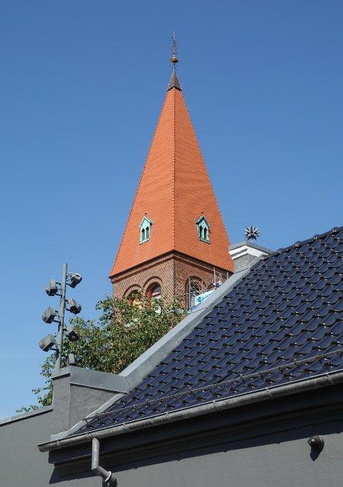 Kirchturm hinter Wohnhaus