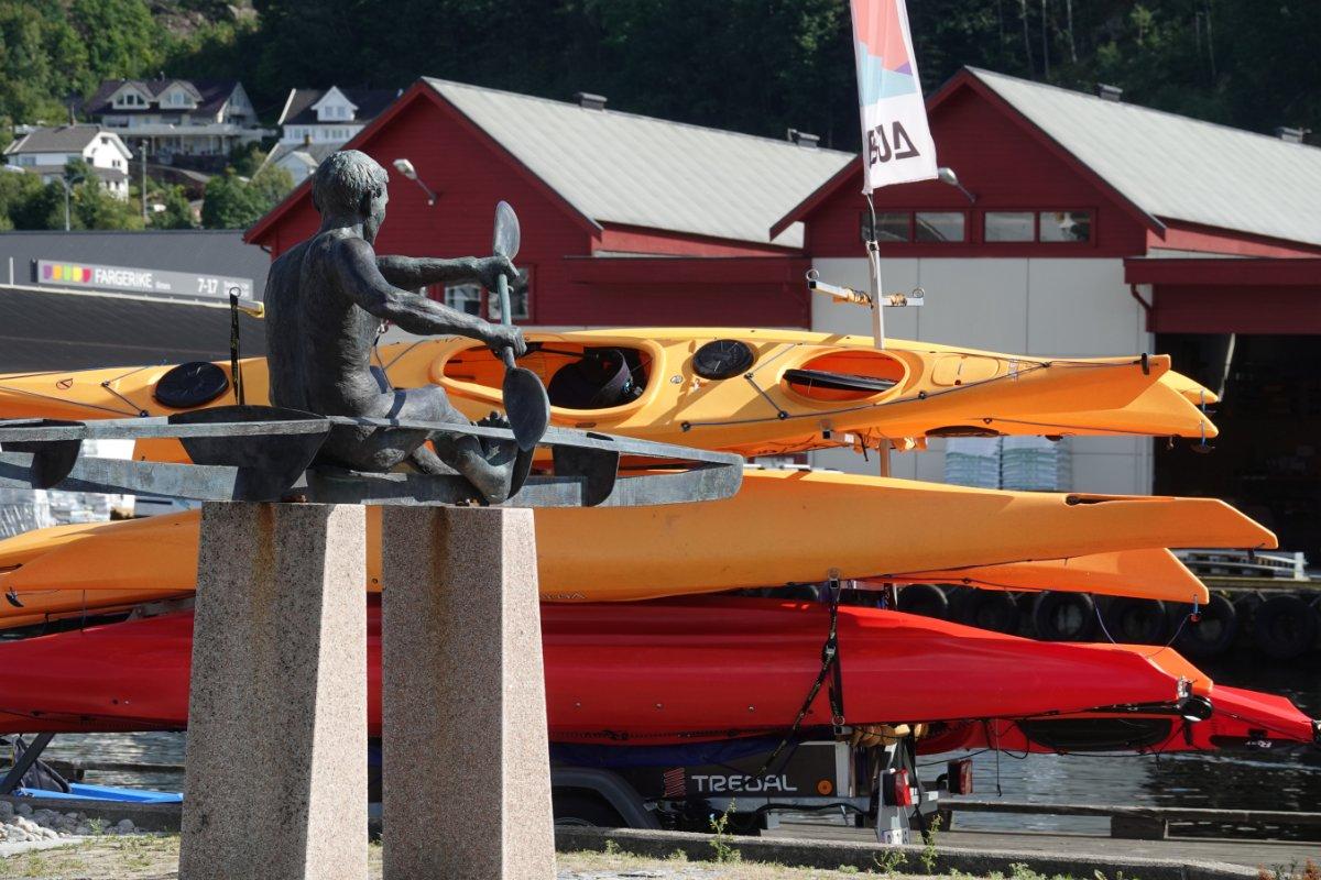 Statue eines Kajakfahrers und bunte Boote